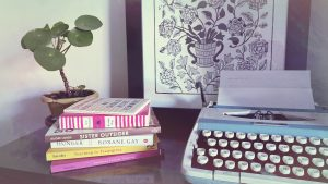 Four books beside a 1960s blue typewriter, next to a small, green potted plant. Behind them a black and white print of flowers in a vase.